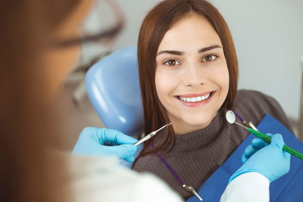 smiling girl treats teeth while sitting in the dental chair at the doctor x
