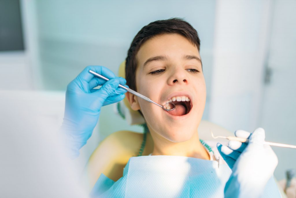 boy with open mouth in dental chair